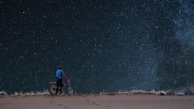 Mężczyzna z bicyklem na tle gwiaździsty niebo zdjęcie wideo