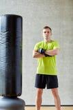 Mężczyzna z bokserskimi rękawiczkami i uderzać pięścią torbą w gym Obrazy Royalty Free