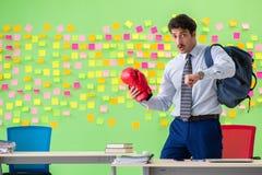 Mężczyzna z bokserskimi rękawiczkami w biurze z wiele sprzeczny przeor zdjęcie stock
