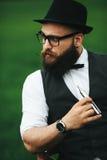 Mężczyzna z brodą dymi elektronicznego papieros fotografia stock