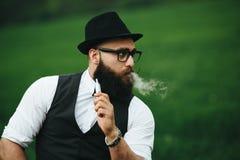 Mężczyzna z brodą dymi elektronicznego papieros fotografia royalty free