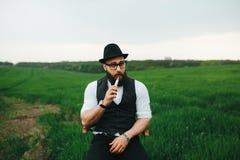 Mężczyzna z brodą dymi elektronicznego papieros zdjęcie stock