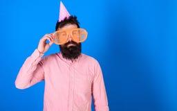 Mężczyzna z brodą i wąsy na spokojnej twarzy osamotnionej na jego urodzinowym, błękitnym tle, Facet w partyjnym kapeluszu świętuj obraz royalty free