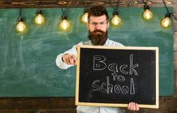Mężczyzna z brodą i wąsy na surowej twarzy ostrzega uczni, wskazuje naprzód, chalkboard na tle tylna szkoły zdjęcie stock
