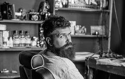 Mężczyzna z brodą i wąsy siedzi w fryzjerach krzesło, piękno dostawy na tle Modniś z brodą czeka obraz royalty free