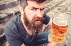 Mężczyzna z brodą i wąsy trzyma szkło z piwem defocused, podczas gdy siedzi na kamiennych schodkach Facet podnosi up szkło z zdjęcie stock