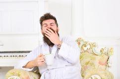 Mężczyzna z brodą i wąsy ziewa podczas gdy siedzący na staromodnym luksusowym karle Mężczyzna śpiący w bathrobe pije kawę Obraz Royalty Free