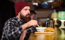 Mężczyzna z brodą je hamburgeru menu Brutalnego modnisia brodaty mężczyzna siedzi przy baru kontuarem Nabranie posiłek Wysoki kal zdjęcie royalty free