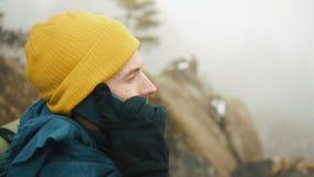 Mężczyzna z brodą, jest ubranym żółtą zimę odziewa opowiadać na telefonie Wycieczkowicz iść w zim górach z plecakiem zdjęcie wideo