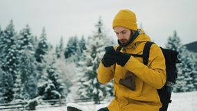 Mężczyzna z brodą, jest ubranym żółtą zimę odziewa używać telefon Wycieczkowicz iść w zim górach z plecakiem zdjęcie wideo