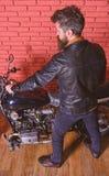 Mężczyzna z brodą, rowerzysta w skórzanej kurtki blisko silnika rowerze w garażu, ściana z cegieł tło Męski hobby pojęcie obraz stock