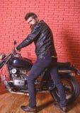 Mężczyzna z brodą, rowerzysta w skórzanej kurtki blisko silnika rowerze w garażu, ściana z cegieł tło Modniś, brutalny rowerzysta zdjęcia stock