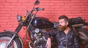 Mężczyzna z brodą, rowerzysta w skórzanej kurtki blisko silnika rowerze w garażu, ściana z cegieł tło Rowerzysty stylu życia poję zdjęcia royalty free
