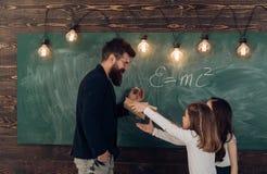 Mężczyzna z brodą w formalnym kostiumu uczy uczennicom physics Nauczyciela i dziewczyn ucznie w sala lekcyjnej blisko chalkboard obraz stock