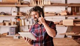 Mężczyzna z brodą w woodwork pracownianym używa telefonie pastylce i obrazy stock
