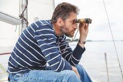 Mężczyzna z brod spojrzeniami przez lornetek na żeglowanie jachcie Fotografia Royalty Free