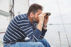 Mężczyzna z brod spojrzeniami przez lornetek na żeglowanie jachcie Zdjęcia Stock