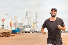 mężczyzna z broda bieg na ulicznym mówieniu z bezprzewodowi hełmofony - słuchawki fotografia stock