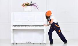 Mężczyzna z broda pracownikiem w hełmie i kombinezonach pcha, wysiłki ruszać się pianino, biały tło Ładowacz rusza się pianino Zdjęcie Stock