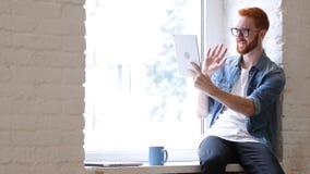 Mężczyzna z brody i rewolucjonistki Hairs Używać pastylkę dla Wideo gadki, Skype, twarz czas zdjęcie stock