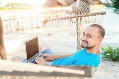 Mężczyzna z brody lying on the beach w hamaku z laptopem Daleka praca obrazy stock