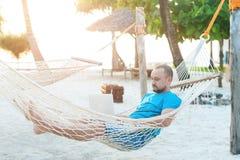 Mężczyzna z brody lying on the beach w hamaku z laptopem Daleka praca zdjęcie royalty free