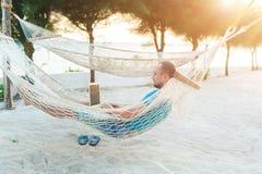 Mężczyzna z brody lying on the beach w hamaku z laptopem Daleka praca fotografia royalty free