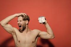 Mężczyzna z budzika poziewaniem na czerwonym tle fotografia stock