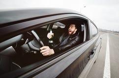 Mężczyzna z butelką piwny jeżdżenie samochód zdjęcia stock
