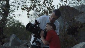 Mężczyzna z chłopiec używa teleskop zdjęcie wideo