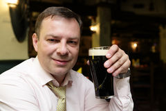 Mężczyzna z ciemnym piwnym kubkiem Zdjęcia Stock