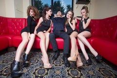 Mężczyzna z cztery dziewczynami na kanapie W wnętrzu Obrazy Stock