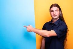 Mężczyzna z długie włosy wskazuje palcem sztandar fotografia stock