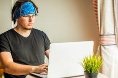Mężczyzna z dreadlocks pracuje na komputerze w domu Fotografia Stock