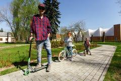 Mężczyzna z dziećmi na hulajnoga Obrazy Royalty Free