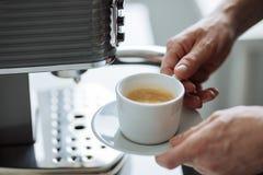Mężczyzna z filiżanką kawa espresso obok kawowego producenta Obrazy Royalty Free