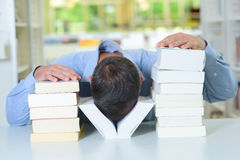 Mężczyzna z głową między dwa stos książkami obraz stock