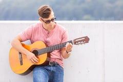 Mężczyzna z gitarą opiera na ścianie Fotografia Stock