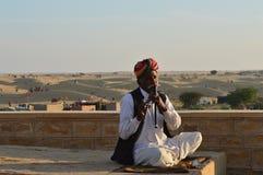 Mężczyzna z instrumentem muzycznym w pustyni Obraz Stock