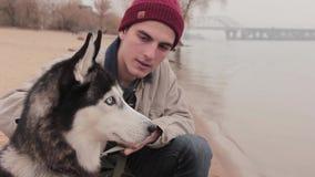 Mężczyzna z jego psim obsiadaniem na plażowym zakończeniu up zdjęcie wideo