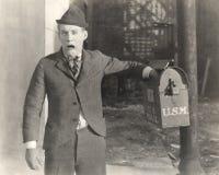 Mężczyzna z jego ręką wtykającą w skrzynce pocztowa zdjęcie royalty free
