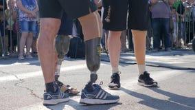Mężczyzna z kalectwem w skrótach z sztuczną nogą w wygodnych sportów butach są trwanie outside na tle tłum zbiory