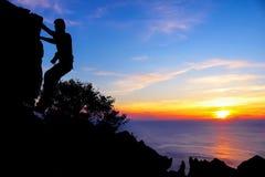 Mężczyzna z kamery pięcia skałą na górze Obrazy Royalty Free
