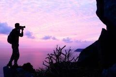 Mężczyzna z kamery pięcia skałą na górze Zdjęcia Royalty Free