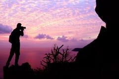 Mężczyzna z kamery pięcia skałą na górze Fotografia Royalty Free