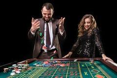 Mężczyzna z kobietą bawić się ruletę przy kasynem Nałóg zdjęcia stock