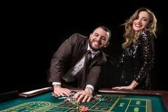 Mężczyzna z kobietą bawić się ruletę przy kasynem Nałóg fotografia royalty free