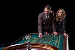 Mężczyzna z kobietą bawić się ruletę przy kasynem Nałóg fotografia stock