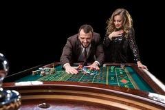Mężczyzna z kobietą bawić się ruletę przy kasynem Nałóg obraz stock