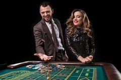 Mężczyzna z kobietą bawić się ruletę przy kasynem Nałóg zdjęcie stock